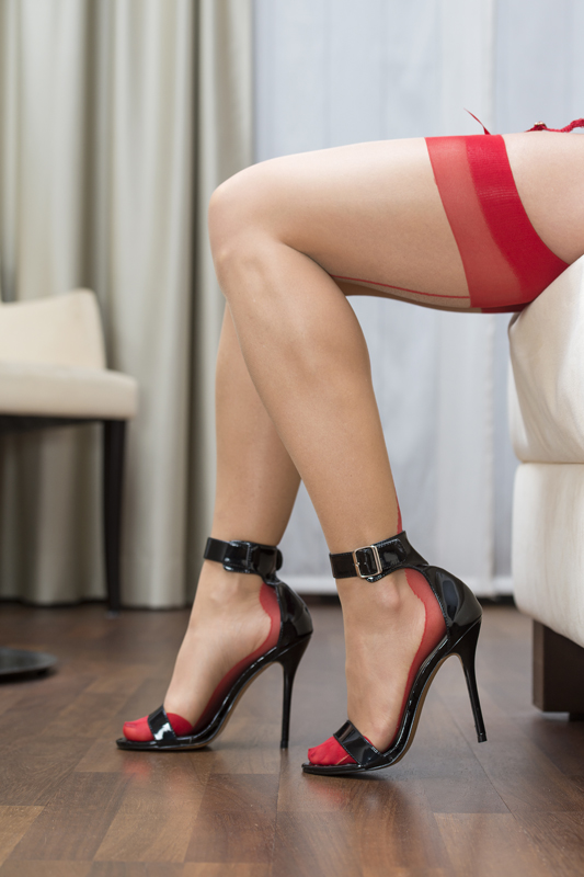 Sexy long legs of a caucasian woman wearing garter belt and stockings in nude and red. With high heels shoes with ankle straps.